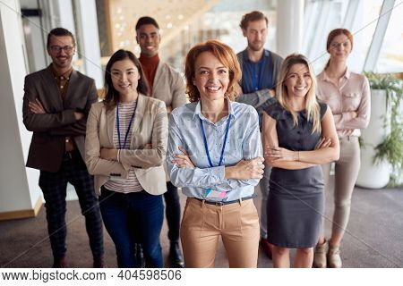 bold and outgoing group of successful business people, looking at camera with team leader in front . eye contact, looking at camera, smiling