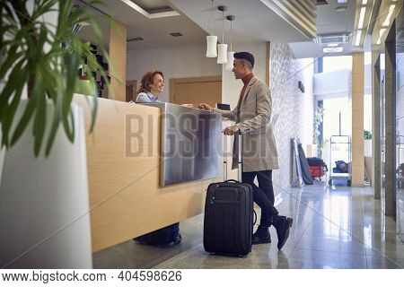 young  afro-american male paying with card to a friendly female caucasian at reception desk at entrence in the hotel