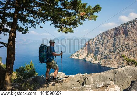 Hiking on Lycian way. Man with backpack enjoys view of Butterfly Valley blue lagoon from rocky cliff in shadow of coniferous tree on Lycian Way trail, Mediterranean coast in Turkey