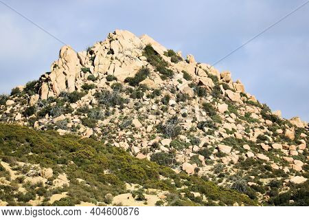 Rural Hillside Covered With Chaparral Plants And Large Rocks And Boulders Taken On Arid Badlands At