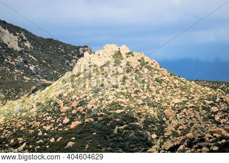 Barren Hills Covered With Large Rocks And Boulders Surrounded By Chaparral Plants Taken On Arid Badl