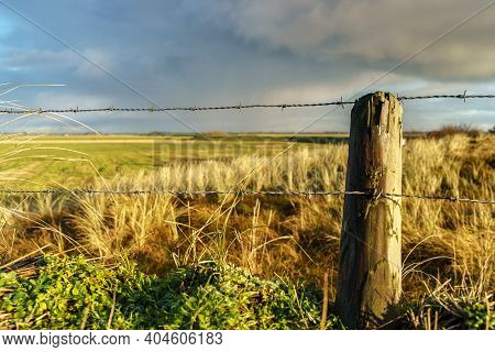 Fence With Barbed Wire And Wooden Post With A View Over The Landscape Of The Wadden Island Of Texel