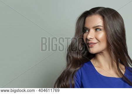 Portrait Of Cheerful Woman With Clear Skin And Dark Wavy Hair On White Background