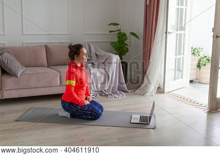 Photo Of A Middle Aged Woman Doring Yoga Workout In Front Of Laptop Monitor. Meditation Practice Onl