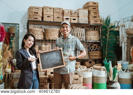 Asian Couple Entrepreneur Holding A Blackboard With Finger Pointing In A Craft Shop