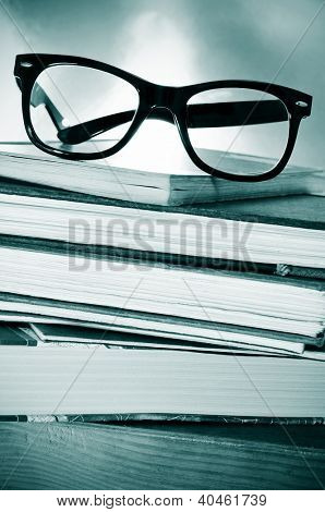 a pile of books and glasses on a desk symbolizing the concept of reading habit or studying