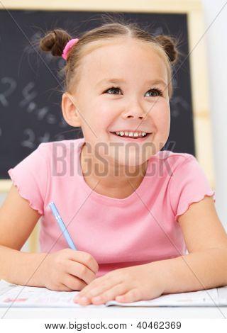 Cute little girl is writing using a pen in school