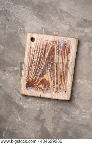 Handcrafted Old Wooden Cutting Board On Stone Concrete Background, Top View