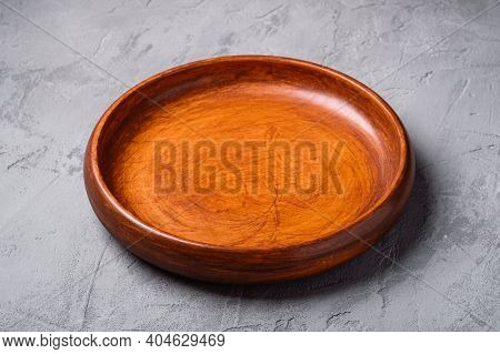 Empty Round Handcrafted Brown Wooden Plate On Stone Concrete Background, Angle View