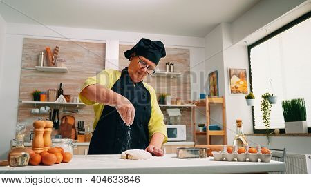 Woman Elderly Cook Sprinkling A Piece Of Dough With Flour. Retired Senior Baker With Bonete And Unif