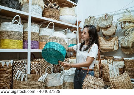 A Girl Selects And Raises A Wicker Basket Stand Against A Background Of Assorted Wicker Crafts