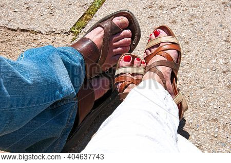 Men\'s And Women\'s Feet In Summer Sandals Relax.