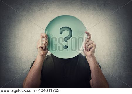 Anonymous Man Hiding His Identity, Covering Face Using An Empty Dish Plate With Question Mark. Globa