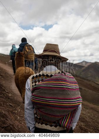 Man In Traditional Andean Indigenous Clothes Hiking With Alpaca At Colorful Palccoyo Rainbow Mountai