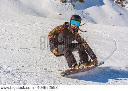 Young Woman Snowboarder In Motion On Snowboard In Mountains.