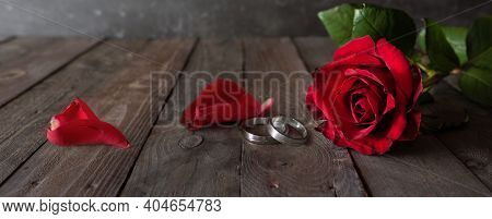 Wedding Rings And Red Roses On Wodden  Vintage Background. Horizontal Romantic Still Life For A Wedd