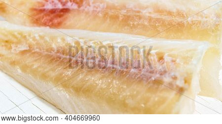 Frozen Pollock Fillet On A White Background. Close-up, Selective Focus.