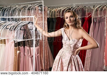 Young Beautiful Blonde Girl Wearing A Full-length Draped One Shoulder Pale Pink Satin Slit Prom Ball