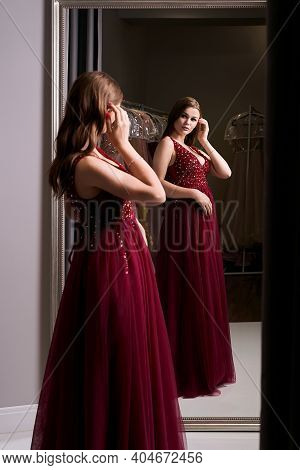 Young Beautiful Brunette Girl Wearing A Full-length Dark Crimson Red Chiffon Prom Ball Gown Decorate
