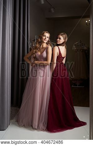 Two Young Beautiful Girls Wearing A Full-length Dark Crimson Red Chiffon Prom Ball Gown Decorated Wi