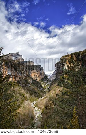 Mountain Scenery With A River Flowing Through It On A Sunny Day With Cotton Clouds, Anisclo Canyon O