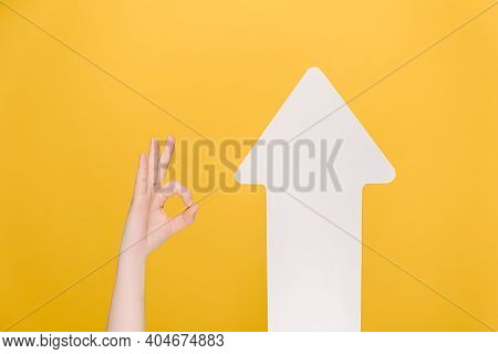 Image Of Unrecognizable Female Makes Thumb Up Gesture Near White Paper Arrow, Demonstrates Approval