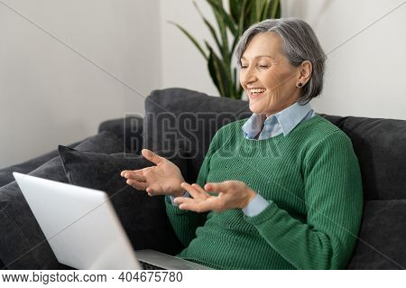 Positive Senior Mature Woman Sitting On The Couch, Laughing And Looking At The Laptop Screen, Watchi