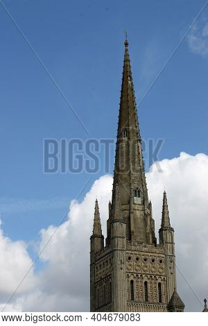 Norwich Cathedral Spire With Further Buildings In The Foreground And A Background Of Blue Sky And Wh