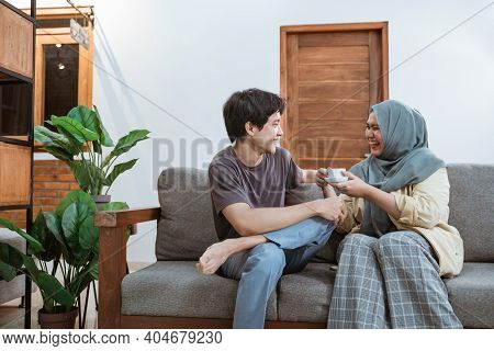 Young Asian Muslimah Couples Chat Jokingly While Enjoying Coffee