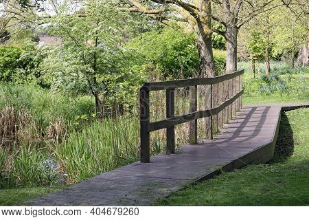 Recycled Plastic Surfaced Boardwalk Path With Wooden Fence Across Wet Marshy Area In Parkland With T