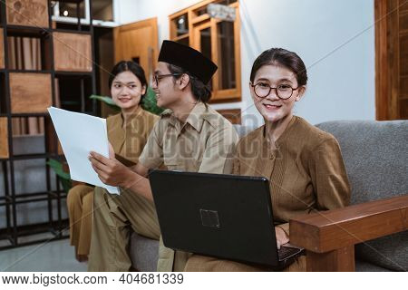 Asian Woman Teacher In Civil Servant Uniform Smiling Looks At The Camera Holding A Laptop Computer
