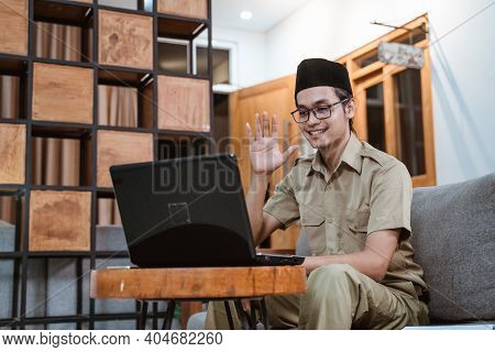 Male Teacher In Civil Servant Uniform And Wearing A Cap Waving In Front Of A Laptop Computer