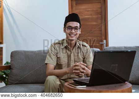 Man In Government Servant Uniform Sitting On The Couch Using A Laptop Computer When Working From Hom