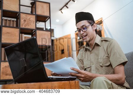 Man In Government Uniform Holding Papers While Working From Home Online