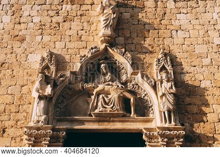 Facade Of The Franciscan Monastery With High Relief Depicting Holy Images In The Old Town Of Dubrovn