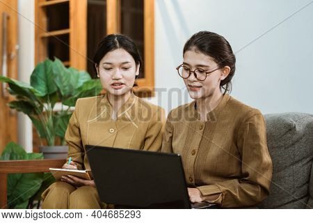 State Official And Assistant In Civil Servant Uniforms Sit Together On Sofa While Working Online Usi