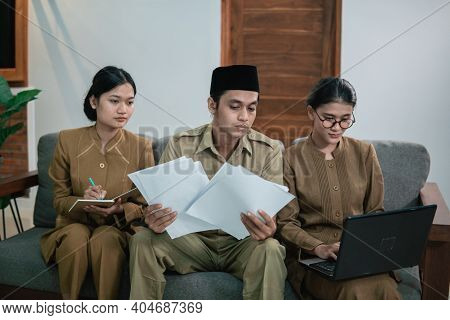A Serious State Official Holding A Paper And Two Female Assistants In Civil Servant Uniforms
