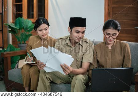 Man And Women Civil Servants Holding Papers And Using Laptops While Working Online Completing Assign