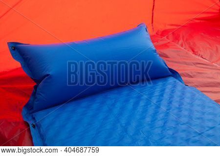 A Blue Self Inflating Blow-up Mattress Pad Is Placed In A Red Tent To Provide A Comfortable Sleep To