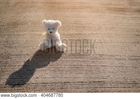 Broken Heart Or Loneliness Concept. Alone Teddy Bear Sitting On Dirty Concrete Road  With Dark Silho