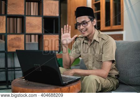 Man In Civilian Uniform Use Laptop While Sitting With Hand Gestures To Say Hello