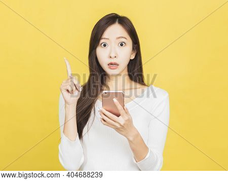 Shocked Young Woman Holding Mobile Phone And Pointing To Copy Space