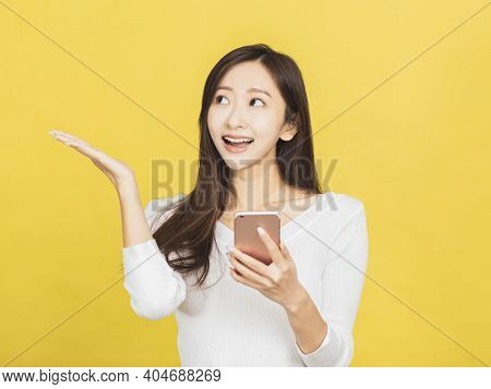 Smiling Casual Young Woman Holding Smartphone And Looking  To Side