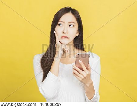Young Woman Holding Smartphone And Thinking About