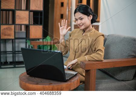 Woman In Civilian Uniform Use Laptop While Sitting With Hand Gestures To Say Hello