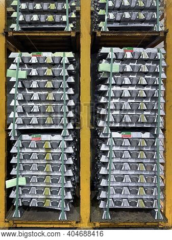 Aluminum Alloy Ingots Stacked On A Yellow Shelf In A Warehouse, With Quality Ok Material Labels, Ver