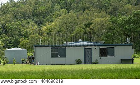 Mackay, Queensland, Australia - January 2021: A Modest Home On The Highway With A Background Of Bush