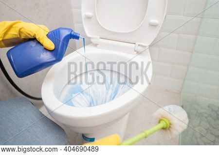 Someone Wearing A Glove Poured Out The Cleaning Liquid And Held The Brush While Cleaning The Toilet