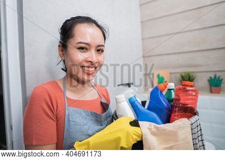 Smiling Woman Wearing Yellow Gloves While Carrying A Bucket Filled With Cleaning Tools And A Bottle