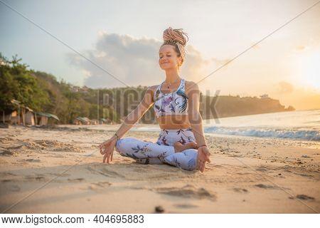 Beautiful Woman Practicing Yoga On The Beach. Sitting In Padmasana, Lotus Pose. Hands In Gyan Mudra.
